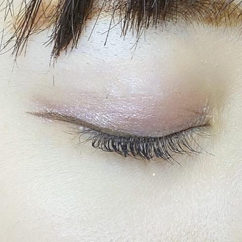 インフルエンサーがスパークリングアイグロスを使用し、目を閉じた写真
