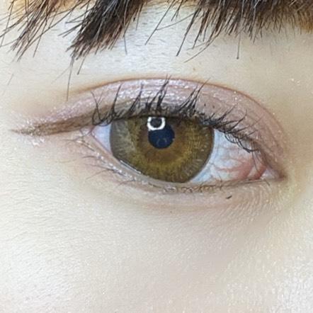 インフルエンサーがスパークリングアイグロスを使用し、目を開いた写真
